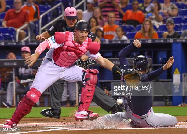Freddie Freeman of the Atlanta Braves slides into home plate for the score in the first inning against the Miami Marlins at Marlins Park on May 13...