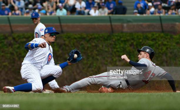 Freddie Freeman of the Atlanta Braves steals second base as Javier Baez of the Chicago Cubs makes a late tag during the sixth inning while wearing...