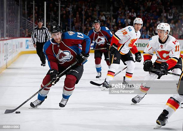 Freddie Hamilton of the Colorado Avalanche controls the puck against Mikael Backlund of the Calgary Flames at Pepsi Center on March 14 2015 in Denver...
