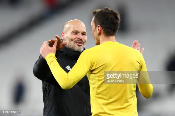 Freddie Ljungberg Interim Manager of Arsenal and Mesut Ozil of Arsenal celebrate victory during the Premier League match between West Ham United and...