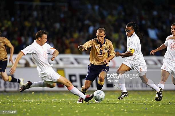 Freddie Ljungberg of Sweden gets tackled by Kevin Hofland whilst under pressure from Edgar Davids of the Netherlands during the International...