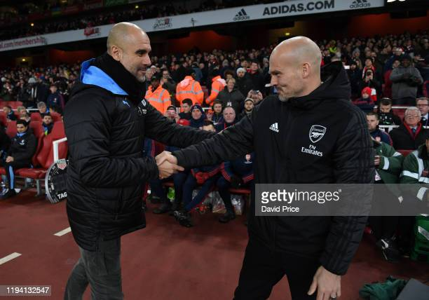 Freddie Ljungberg the Arsenal Interim Head Coach shakes hands with Man City Head Coach Pep Guardiola before the Premier League match between Arsenal...
