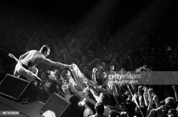 Freddie Mercury du groupe Queen serre des mains dans la foule de ses fans lors d'un concert le 18 septembre 1984 à Paris France