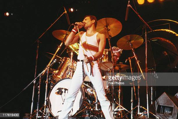Freddie Mercury singer with Queen standing in front of a drumkit as he sings into a microphone on stage during a live concert performance by the band...