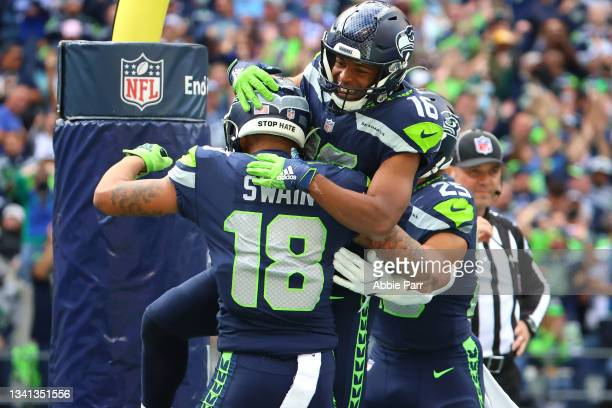 Freddie Swain celebrates his 68-yard touchdown with Tyler Lockett of the Seattle Seahawks against the Tennessee Titans during the fourth quarter at...