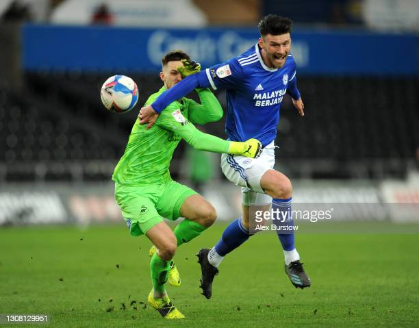 Freddie Woodman of Swansea City and Kieffer Moore of Cardiff City battle for the ball during the Sky Bet Championship match between Swansea City and...