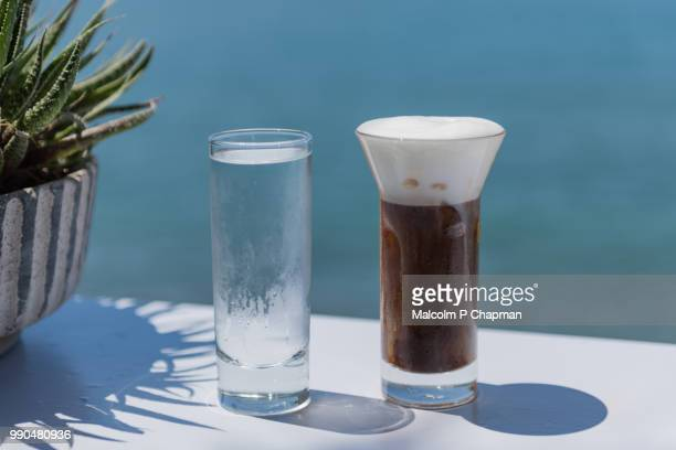 freddo cappuccino - iced cappuccino coffee drink served with water, lesvos, greece - lesbos stock photos and pictures