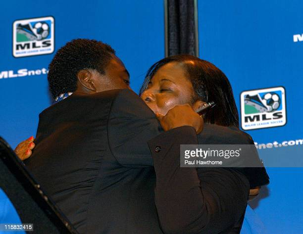 Freddy Adu hugs his mother Emeila, after giving her the pen he used to sign his contract with during a news conference announcing his multi year deal...