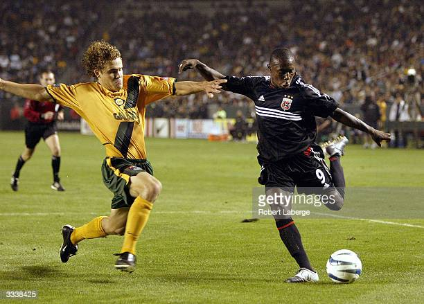 Freddy Adu of DC United shoots under pressure from Chris Albright of the Los Angeles Galaxy during the MLS game on April 10 2004 at the Home Depot...