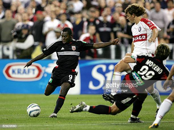 Freddy Adu of DC United takes a shot on goal past teammate Jaime Moreno and Kelly Gray of the Chicago Fire as DC United deteated the Fire 10 during...