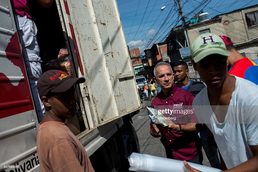 Freddy Bernal, former Caracas mayor and current CLAPs overseer, center, helps unload a truck of groceries in the Catia neighborhood on the outskirts of Caracas, Venezuela, on Saturday, July 2, 2016. In an attempt to regain control, President Nicolas Maduro has tapped loyal neighborhood groups, called Local Committees for Supply and Production (CLAPs), and put them in charge of distributing as much as 70 percent of the nation's food. Photographer: Manaure Quintero/Bloomberg via Getty Images