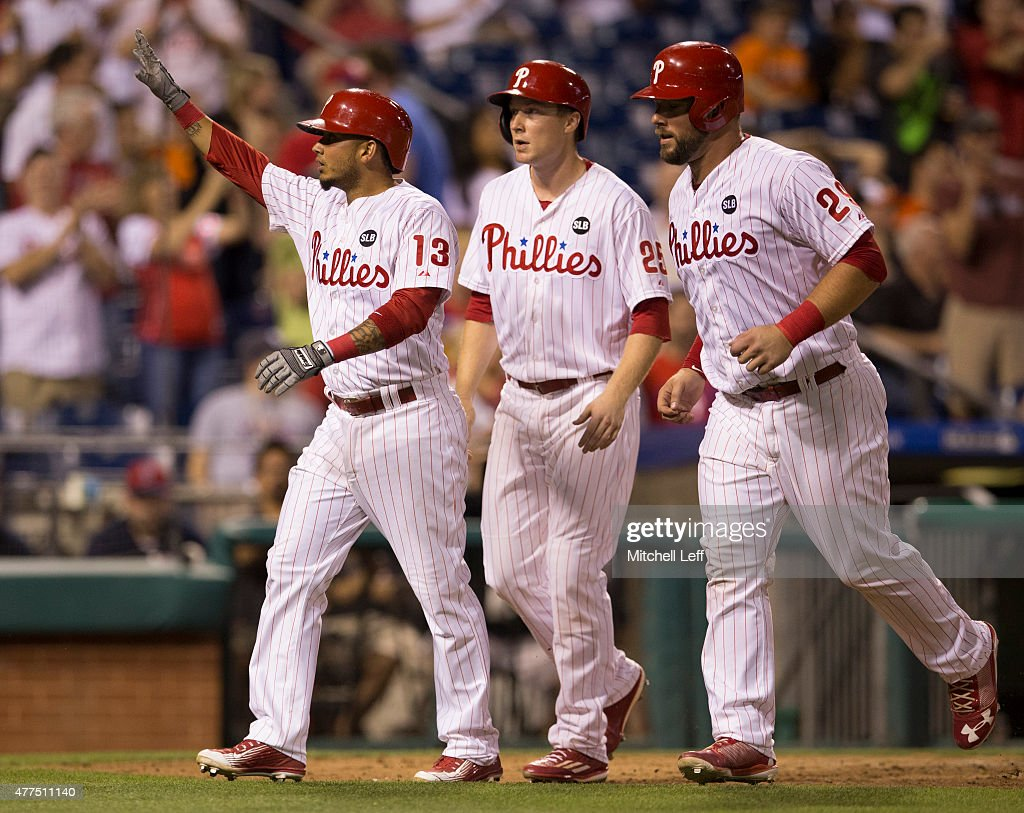 Freddy Galvis #13, Cody Asche #25, and Cameron Rupp #29 of the Philadelphia Phillies walk back to the dugout after Galvis hit a three run home run in the bottom of the seventh inning against the Baltimore Orioles on June 17, 2015 at the Citizens Bank Park in Philadelphia, Pennsylvania. The Orioles defeated the Phillies 6-4.