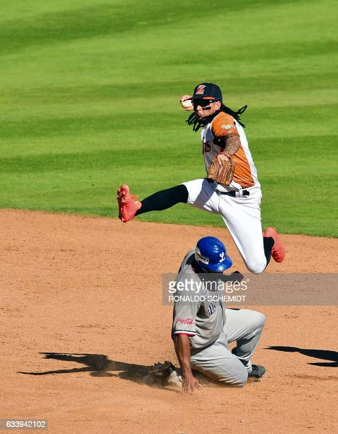 Freddy Galvis of Aguilas del Zulia of Venezuela tags out Mel Rojas of Tigres del Licey of the Dominican Republic in second base during the Caribbean...