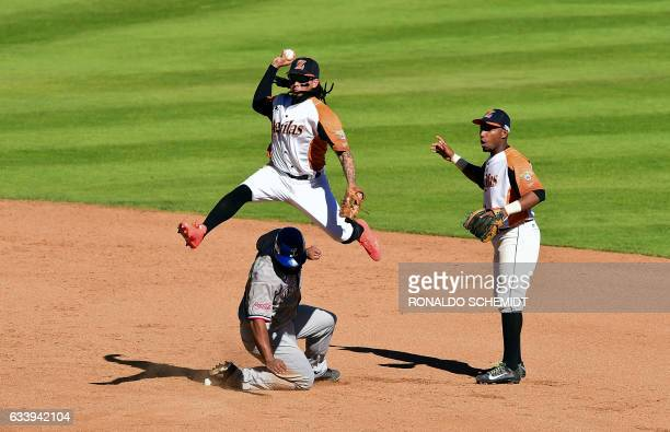 TOPSHOT Freddy Galvis of Aguilas del Zulia of Venezuela tags out Mel Rojas of Tigres del Licey of the Dominican Republic in second base during the...