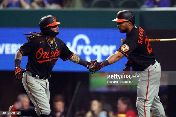 Freddy Galvis of the Baltimore Orioles is greeted by Anthony Santander after scoring on a double by Cedric Mullins against the Texas Rangers in the...