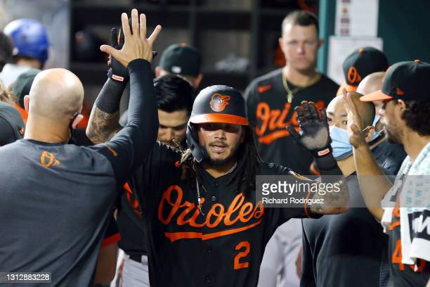 Freddy Galvis of the Baltimore Orioles is greeted in the dugout after scoring on a double by Cedric Mullins in the third inning against the Texas...