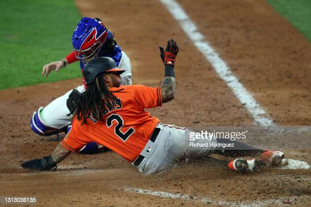 Freddy Galvis of the Baltimore Orioles slides into home past Jonah Heim of the Texas Rangers to score on a single by Cedric Mullins in the seventh...