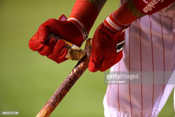 Freddy Galvis of the Philadelphia Phillies applies pine tar to his bat as he stands in the ondeck circle during a game against the Colorado Rockies...