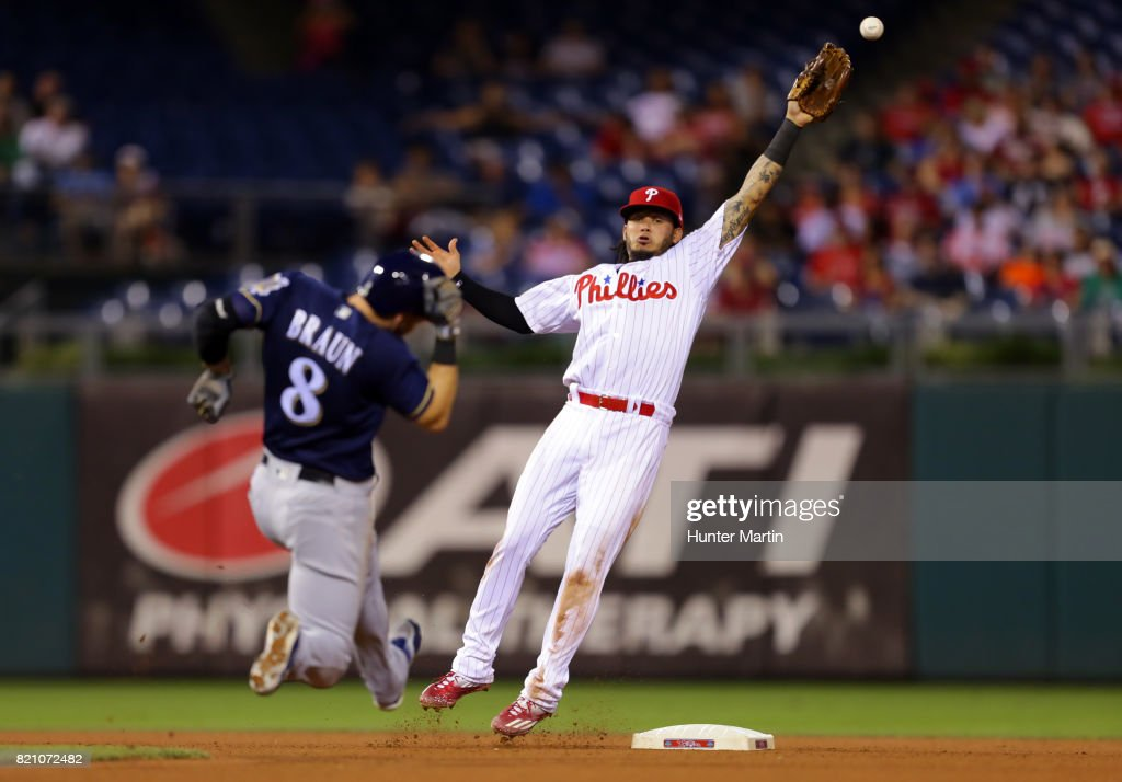Freddy Galvis #13 of the Philadelphia Phillies attempts to catch a throw as Ryan Braun #8 of the Milwaukee Brewers slides safely into second base in the seventh inning during a game at Citizens Bank Park on July 22, 2017 in Philadelphia, Pennsylvania. The Brewers won 9-8.