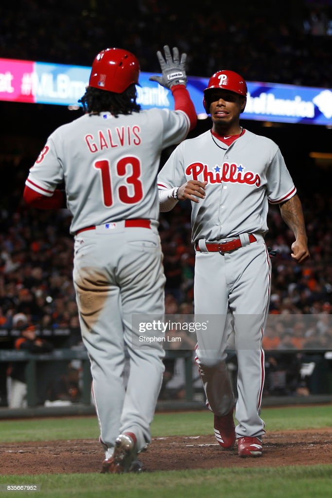 Freddy Galvis #13 of the Philadelphia Phillies high fives teammate Nick Williams #5 after scoring on a Ty Kelly #15 grand slam during the sixth inning against the San Francisco Giants at AT&T Park on August 19, 2017 in San Francisco, California.