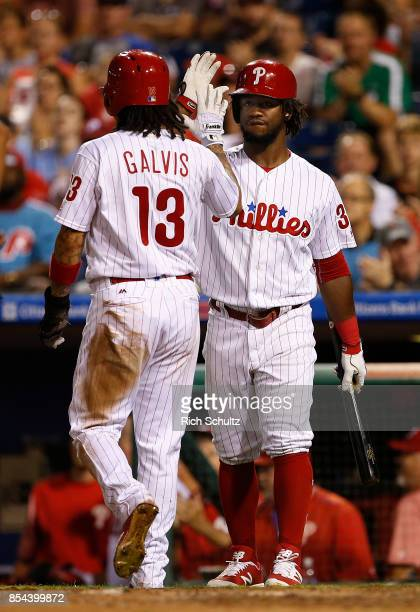 Freddy Galvis of the Philadelphia Phillies is congratulated by Odubel Herrera after scoring on a single by Tommy Joseph against the Washington...