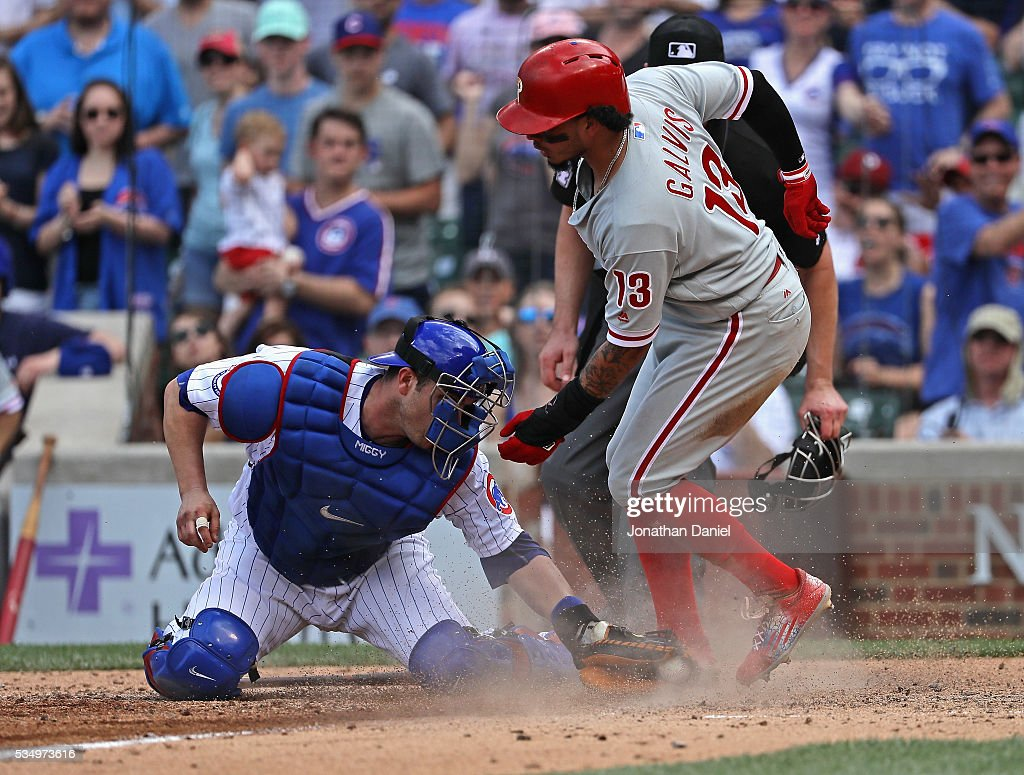 Freddy Galvis #13 of the Philadelphia Phillies scores a run in the 9th inning as Miguel Montero #47 of the Chicago Cubs attempts the tag at Wrigley Field on May 28, 2016 in Chicago, Illinois. The Cubs defeated the Phillies 4-1.