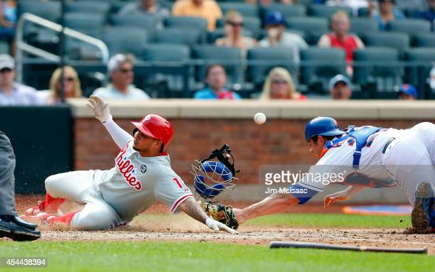 Freddy Galvis of the Philadelphia Phillies scores a seventh inning run as Anthony Recker of the New York Mets can't hold onto the ball at Citi Field...