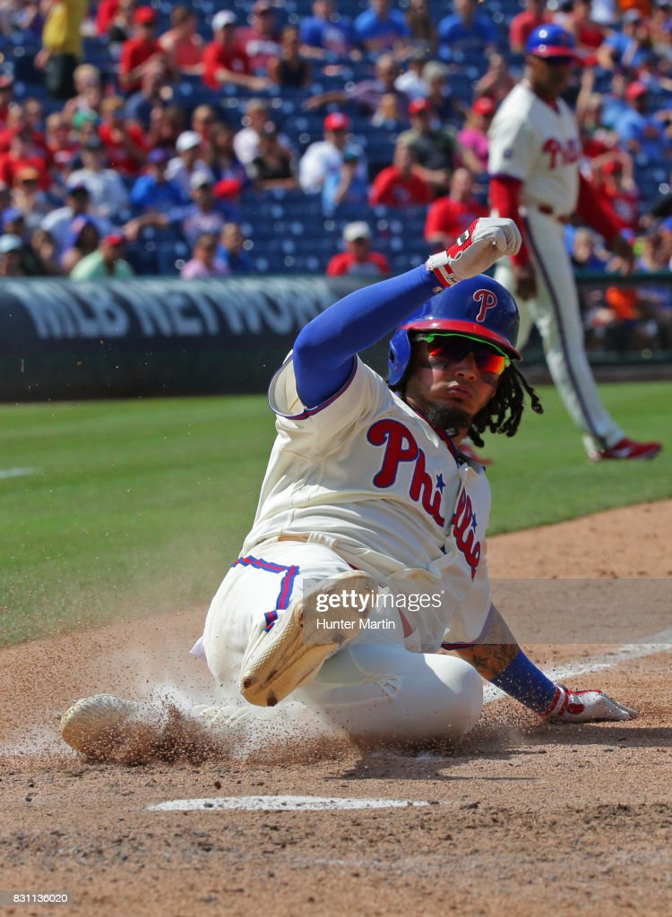 Freddy Galvis #13 of the Philadelphia Phillies slides home safely after a wild pitch in the fifth inning during a game against the New York Mets at Citizens Bank Park on August 13, 2017 in Philadelphia, Pennsylvania. The Mets won 6-2.