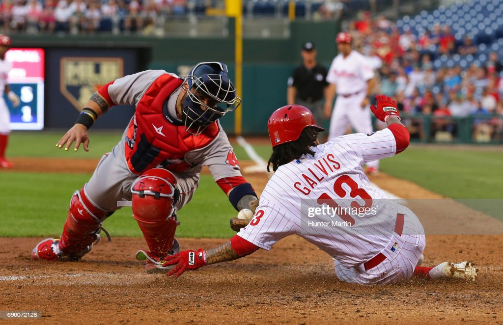 Freddy Galvis #13 of the Philadelphia Phillies slides home safely in front of the tag by Sandy Leon #3 of the Boston Red Sox in the third inning during a game at Citizens Bank Park on June 14, 2017 in Philadelphia, Pennsylvania.