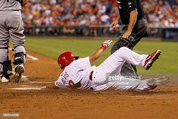 Freddy Galvis of the Philadelphia Phillies slides into home to score a run in the seventh inning of the game against the San Diego Padres at Citizens...