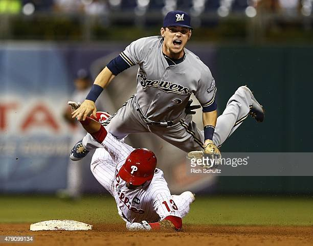 Freddy Galvis of the Philadelphia Phillies slides into second baseman Scooter Gennett of the Milwaukee Brewers after Gennett throws to first to get...
