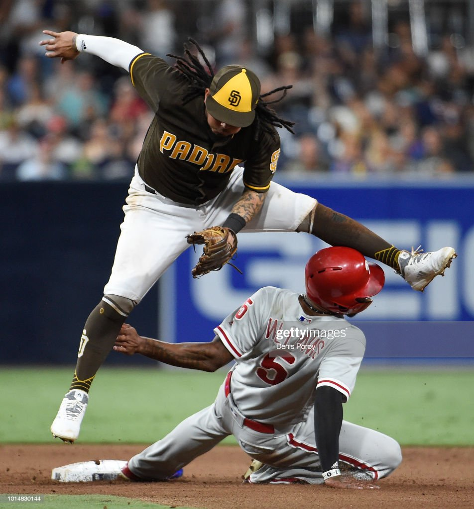 Freddy Galvis #13 of the San Diego Padres jumps over Nick Williams #5 of the Philadelphia Phillies as he turns a double play during the eighth inning of a baseball game at PETCO Park on August 10, 2018 in San Diego, California.