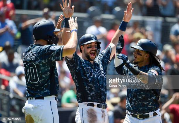 Freddy Galvis of the San Diego Padres right is congratulated by Austin Hedges center and Eric Hosmer after hitting a grand slam during the third...