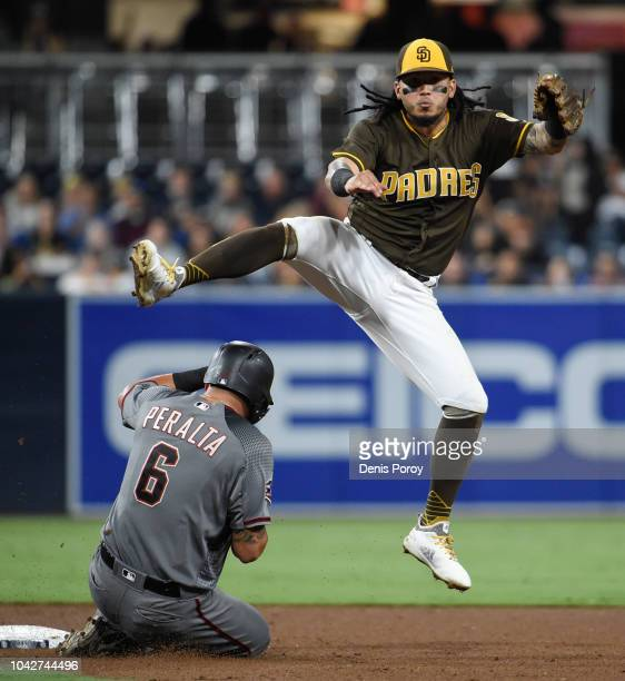 Freddy Galvis of the San Diego Padres throws over David Peralta of the Arizona Diamondbacks as he turns a double play during the sixth inning of a...