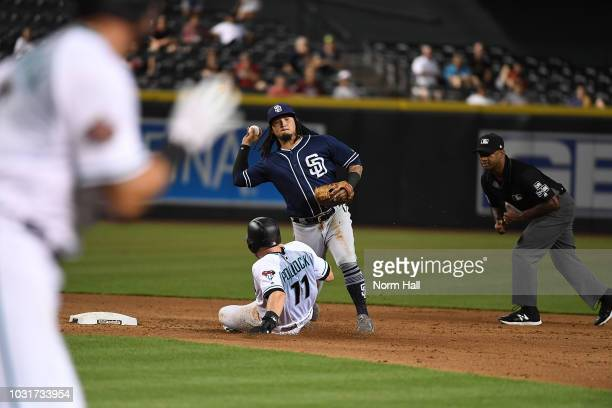 Freddy Galvis of the San Diego Padres turns a double play as AJ Pollock of the Arizona Diamondbacks slides into second base as second base umpire...