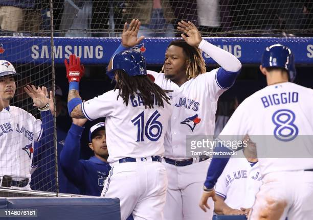 Freddy Galvis of the Toronto Blue Jays is congratulated by Vladimir Guerrero Jr #27 after hitting a tworun home run in the fifth inning during MLB...