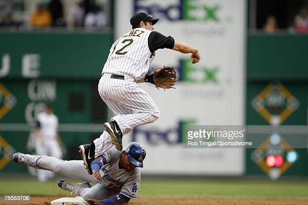 Freddy Sanchez of the Pittsburgh Pirates jumps as Rafael Furcal of the Los Angeles Dodgers slides into second base on June 3, 2007 at PNC Park in...