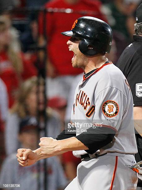 Freddy Sanchez of the San Francisco Giants celebrates after scoring the goahead run off an error by Brooks Conrad of the Atlanta Braves in the ninth...