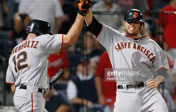 Freddy Sanchez of the San Francisco Giants celebrates with Nate Schierholtz after scoring the goahead run off an error by Brooks Conrad of the...