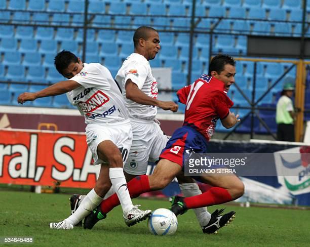 Freddy Thompson de Comunicaciones comete penal a Carlos Figueroa delantero del Municipal junto a su compañero Hector de Mata en el estadio Mateo...