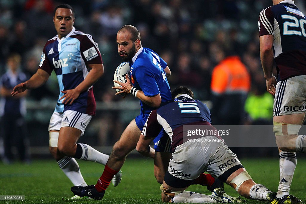 Frederic Michalak of France is tackled by Culum Retallick of the Blues during the tour match between the Auckland Blues and France at North Harbour Stadium on June 11, 2013 in Auckland, New Zealand.