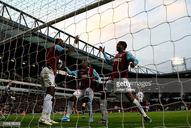 Frederic Piquionne of West Ham congratulates team mate Carlton Cole on scoring the opening goal during the Barclays Premier League match between West...