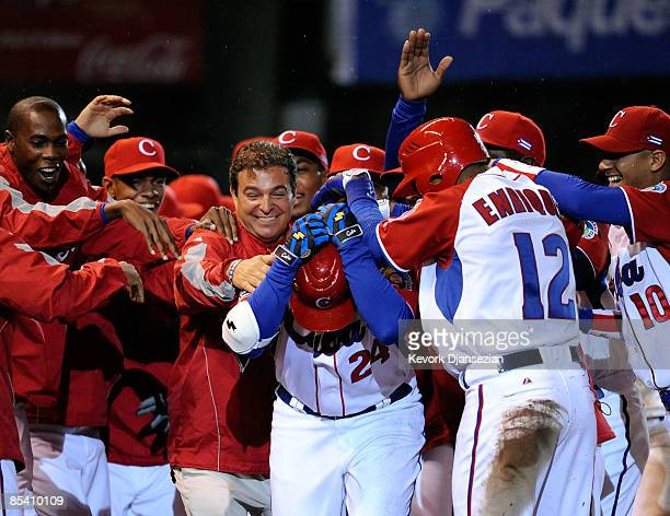 Frederich Cepeda of Cuba is mobbed by his teammates and team doctor Antonio Castro son of former president of Cuba Fidel Castro after hitting a...