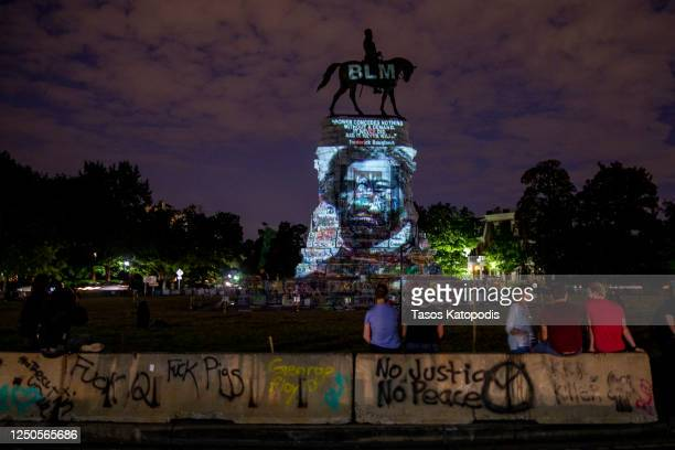 Frederick Douglass's image is projected on the Robert E. Lee Monument as people gather around on June 18, 2020 in Richmond, Virginia. Richmond...