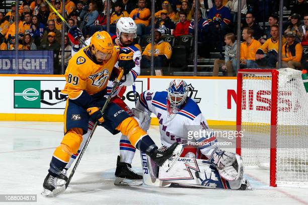 Frederick Gaudreau of the Nashville Predators kicks at a puck in front of Adam McQuaid and goalie Henrik Lundqvist of the New York Rangers during the...
