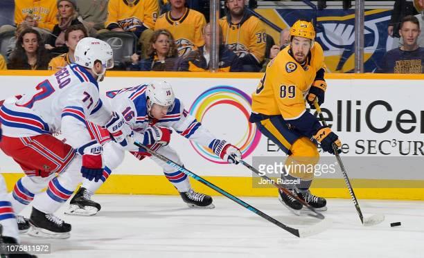 Frederick Gaudreau of the Nashville Predators skates the puck down low against Ryan Strome and Tony DeAngelo of the New York Rangers at Bridgestone...