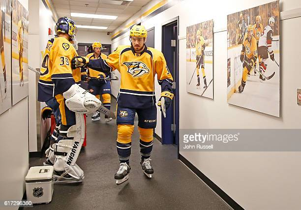 Frederick Gaudreau taps goalie Marek Mazanec of the Nashville Predators as he walks out for his first NHL game on October 22 2016 at Bridgestone...