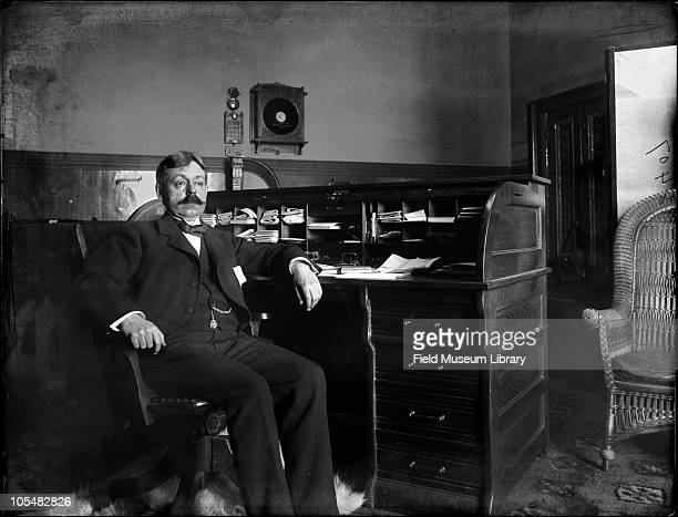 Frederick JV Skiff in his office He is seated on a chair his arm is resting on the wood rolltop desk which is filled with compartments holding papers...