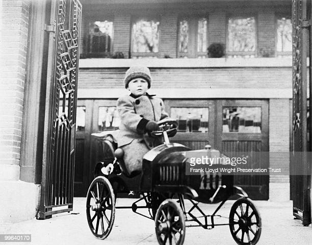 Frederick Robie Jr by courtyard gate in child's car designed by Frederick Robie Sr Chicago Illinois 1911