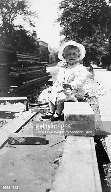 Frederick Robie Jr sitting by pile of lumber at construction site Chicago Illinois 1909